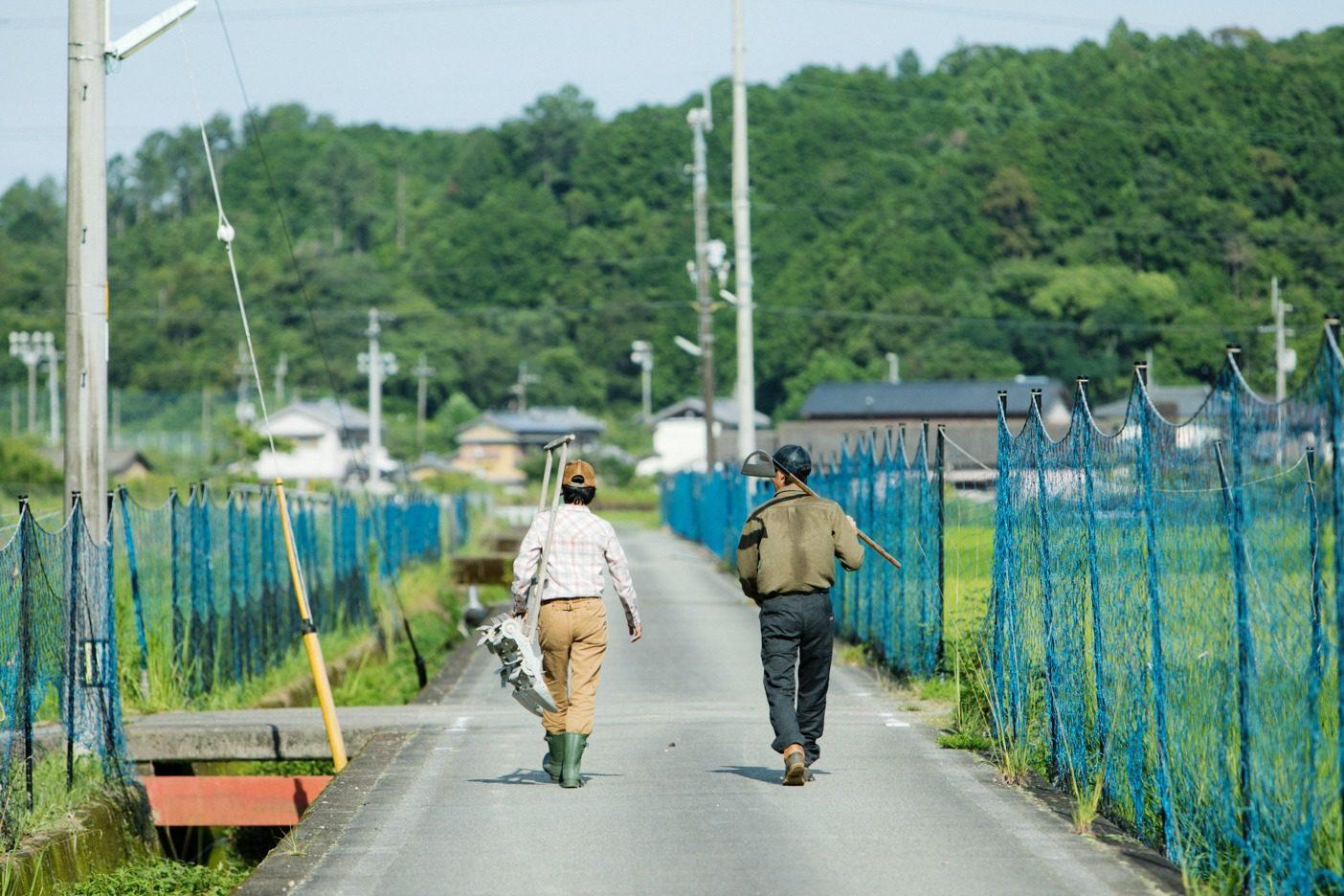 夫婦で仲良く田んぼに向かう。美子さんが持っているのは、昔ながらの手押しの除草機。この時期に欠かせない農具の一つだ。写真:五十嵐 一晴