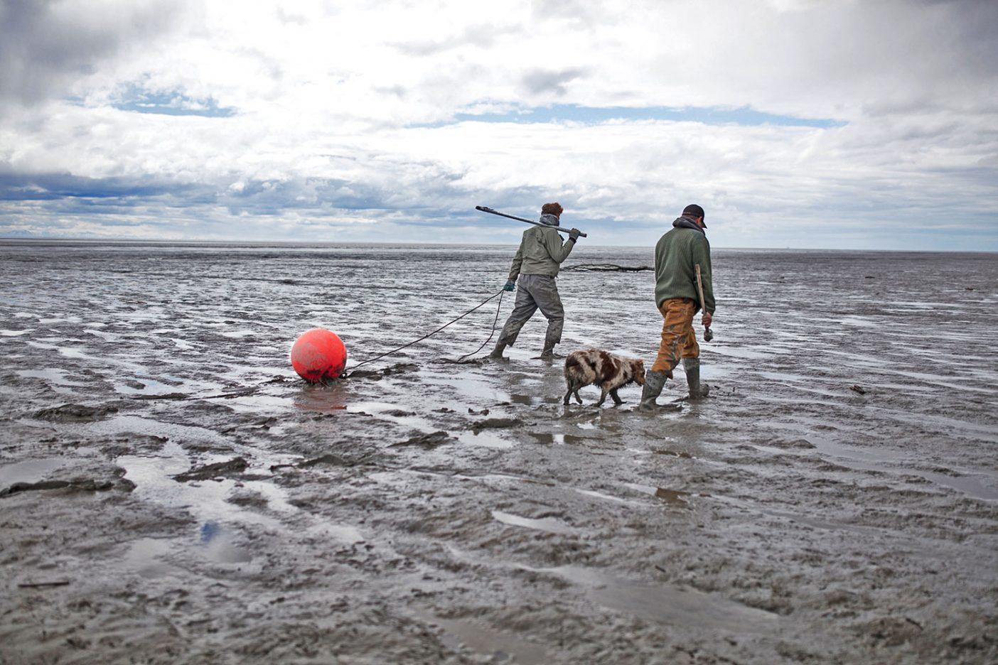 アラスカ州スシトナ・リバーの河口付近に据え付けられた網に向かうライアン・ピーターソンとマイク・ウッド。Photo: Travis Rummel