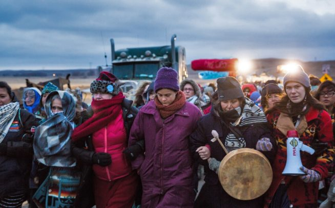 バリケードへ向かう。2016年、ノースダコタ州のスタンディング・ロック・スー族居留地にある機動隊のバリケードに到達するウィメンズ・マーチ。#NoDAPLの抗議は、先住民の権利だけでなく、気候危機が激しくなるにしたがって私たち全員が直面する罰に焦点を当てた。私たちが守るべきは石油会社なのか?淡水なのか? Photo: Colin McCarthy