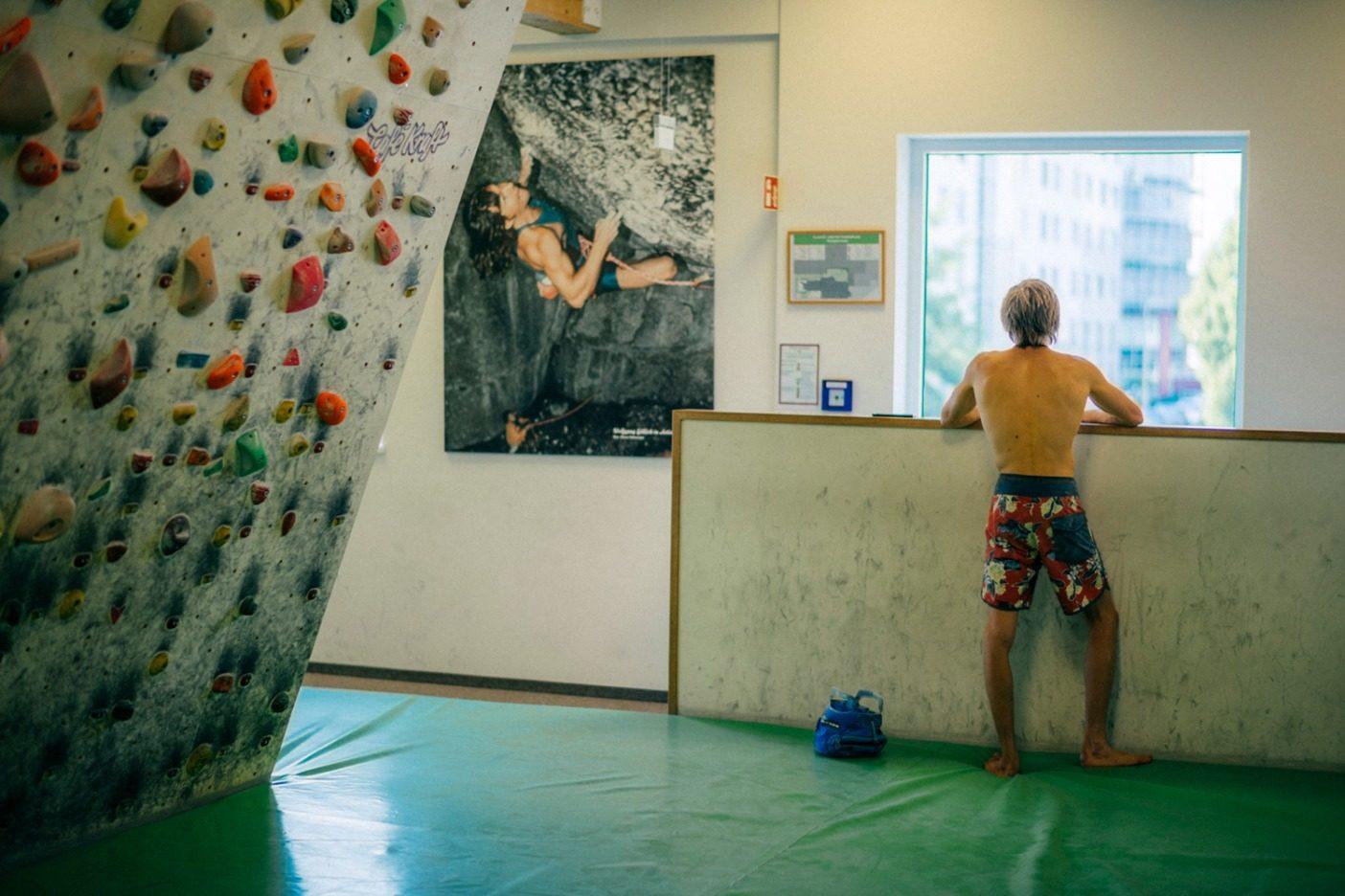 「アクション・ディレクト」を登る伝説的なヴォルフガング・ギュリッヒのポスターが見守るなか、トレーニングから休憩するアレックス。ドイツ、エアランゲン。Photo: Ken Etzel