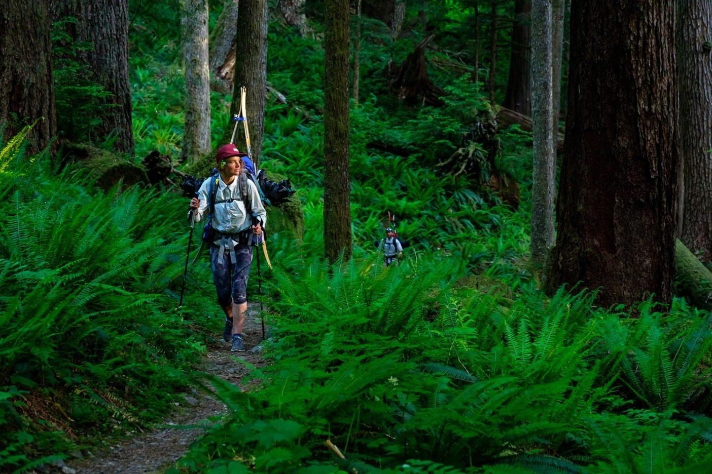 オリンピック山脈での8日間のトラバースの7日目、ホー・リバー・トレイルの上流沿いを下るマリー-フランス・ロイとケール・マーティン。湿ったスノーボード・ブーツをやっと脱ぎ、乾いた靴に履き替えて温帯降雨林を歩いていると、夕日が原生林を金色に染めた。Photo: Colin Wiseman