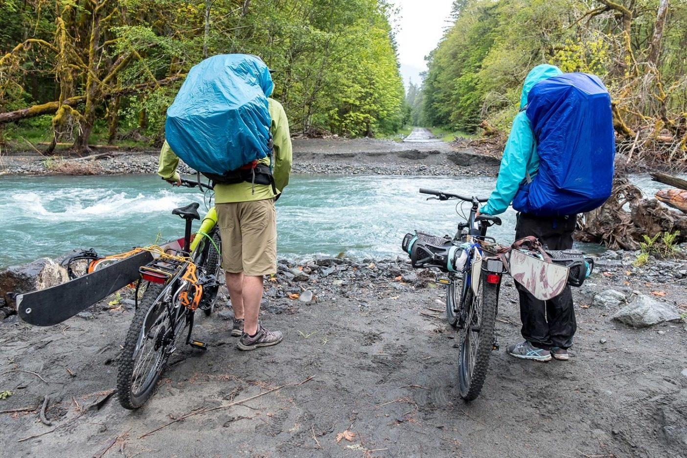 野生の川は野生的なことをする。エルワ・リバーの氾濫による道の崩壊を目にし、オリンパス山へ自転車で行くことの中断を検討するマリー-フランス・ロイとケール・マーティン。Photo: Colin Wiseman