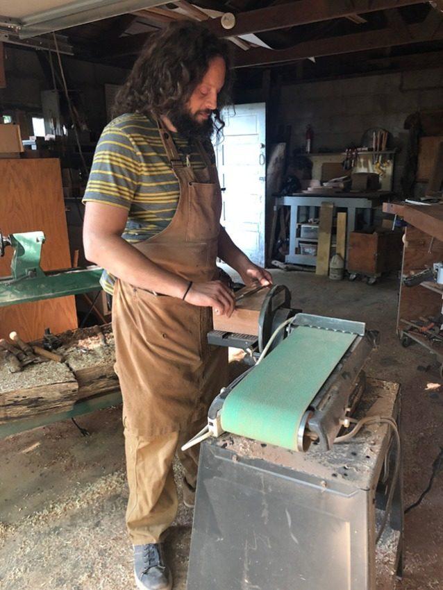 ジョンはベルトサンダー(愛称「カーネル・サンダース」)を使用して板材を整え、接着してブランク材を作る。Photo: Anni Furniss