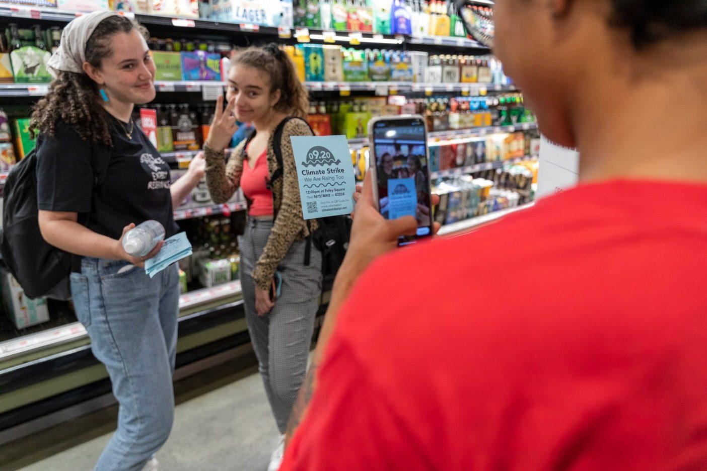 ストライキ前夜にマンハッタンのデリカテッセン内でストライキのチラシを配る主催者のオリビアとイザベラ。「できるかぎりストライキの組織作りをつづけていくつもりです」とオリビアは言う。Photo: Keri Oberly