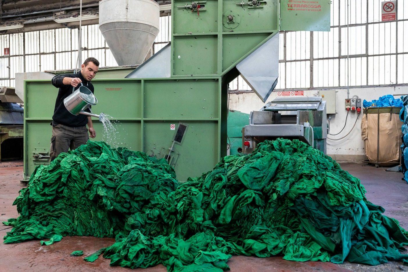 リサイクルされたウール廃棄物を細断機にかける準備をするガブリエル・ミケローニ。衣類のリサイクルは、それを回収し、分別し、細断し、梳き、紡ぎ、織り、布地を新たな生命へと準備する専門ビジネスのネットワークに依存している。この機械はリサイクル・ウールの細断に使われる。 Photo: Keri Oberly