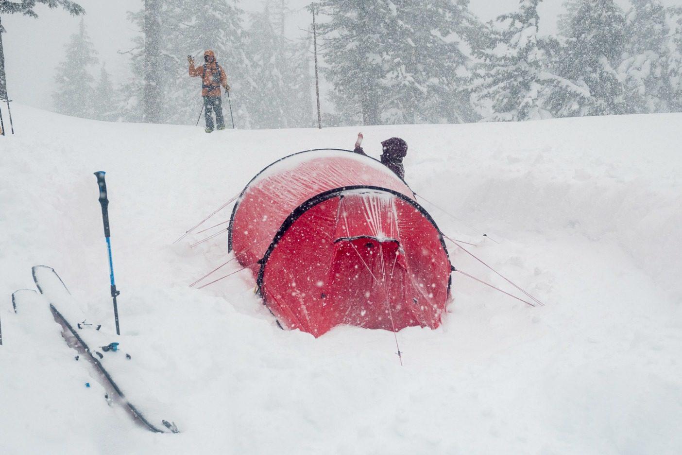 「おかえりなさい、ケイル!」リア・エヴァンスが、ホワイトアウトの中、キャンプの下での短時間の滑降から戻ってきたケイル・マーティンを迎える。Photo: Colin Wiseman