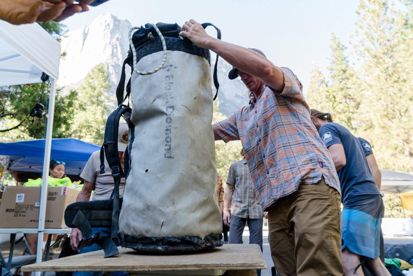 清掃作業後、30キログラムを超える運搬袋を秤に乗せるバド・ミラー。Photo: Eric Bissell