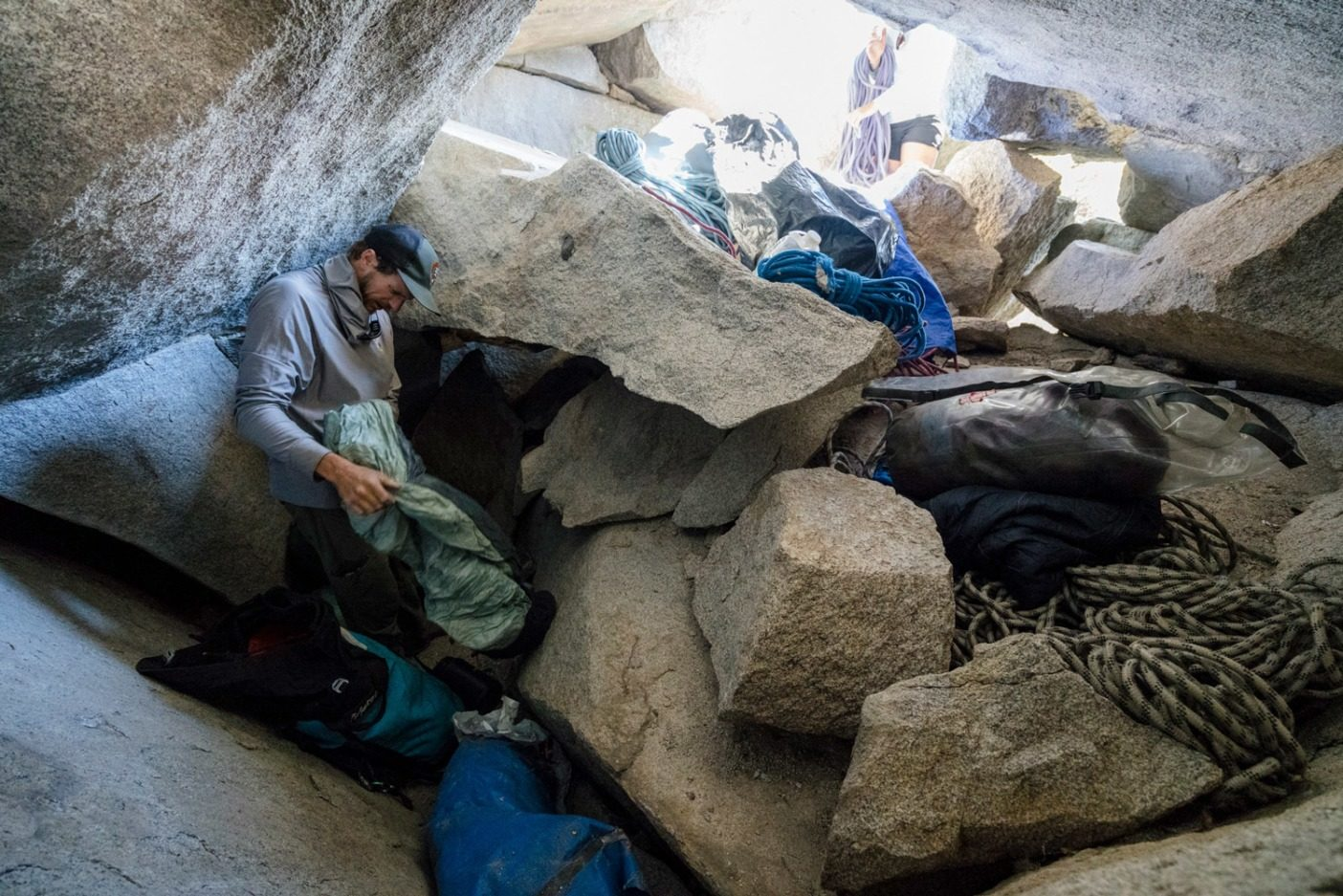 洞穴の中に残された、古いロープやその他のギアが入ったバッグをくまなく調べるクライミング・レンジャーのブランドン・アダムスPhoto: Eric Bissell