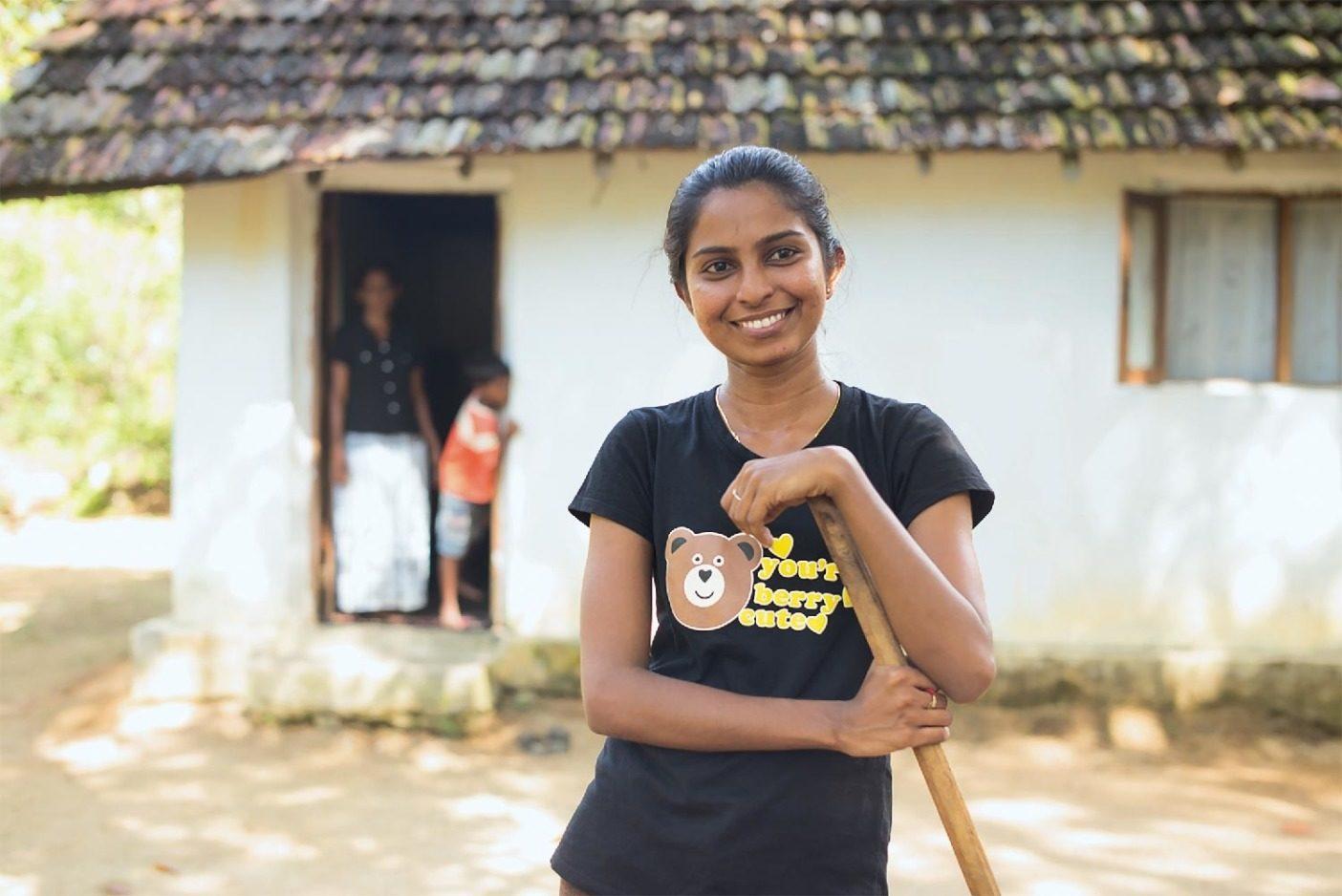 スリランカのパンティヤから30分のところにある自宅の前に立つサンドゥニ・マドゥーシャ。サンドゥニはフェアトレード・サーティファイド縫製の製品を製造するスリランカの提携施設で働く。アジアのパタゴニア現場マネージャーによると、2017年のスリランカのモンスーンは生命に関わるような洪水を起こし、多くの労働者が出勤できなかった。Photo:Tim Davis
