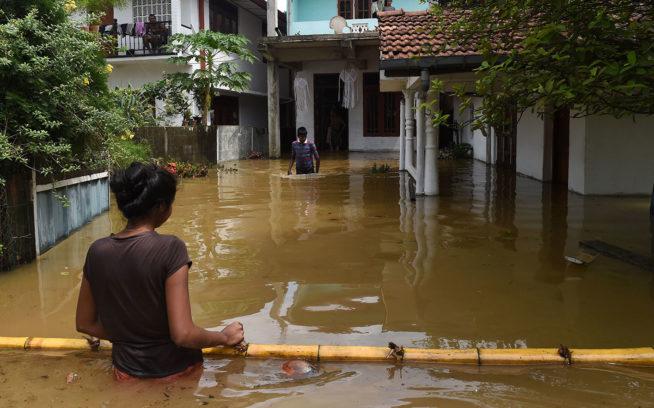 浸水したカドゥウェラ市の家屋の外に立ち尽くすスリランカ人。2017年5月にスリランカを襲った大嵐は、島の南部と西部にこの14年間で最悪の洪水と地滑りをもたらした。こうした異常気象は、人類がひき起こした気候変動により、件数と強さが増大している。Photo:Ishara S. Kodikara/AFP/Getty Images
