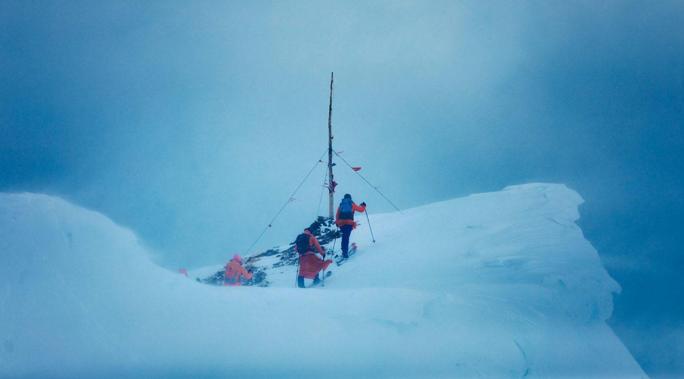 レッド・レディの山頂にたどり着く地元のスキーヤーたち。コロラド州クレステッド・ビュートから 近いエルク山脈にあるレッド・レディの 頂を、独自の祈祷旗の冠で飾りなおす ことは、この地域における同山の重要 な役割を称えるために行われる。Photo: Forest Woodward