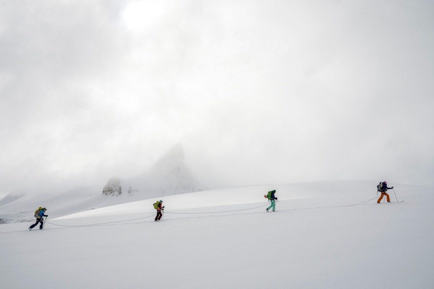 ボウ氷河の高域に向かって登りながら、チームは象徴的であるセント・ニコラス・ピークの下をトラバースする。数日間の嵐の後、雲が薄くなり始め、山は姿を隠していた覆いを外した。若々しい「スキー大好き人間」がすぐにスキーラインを見つけ出すだろうと私たちには分かっていた。Photo:Kennan Harvey