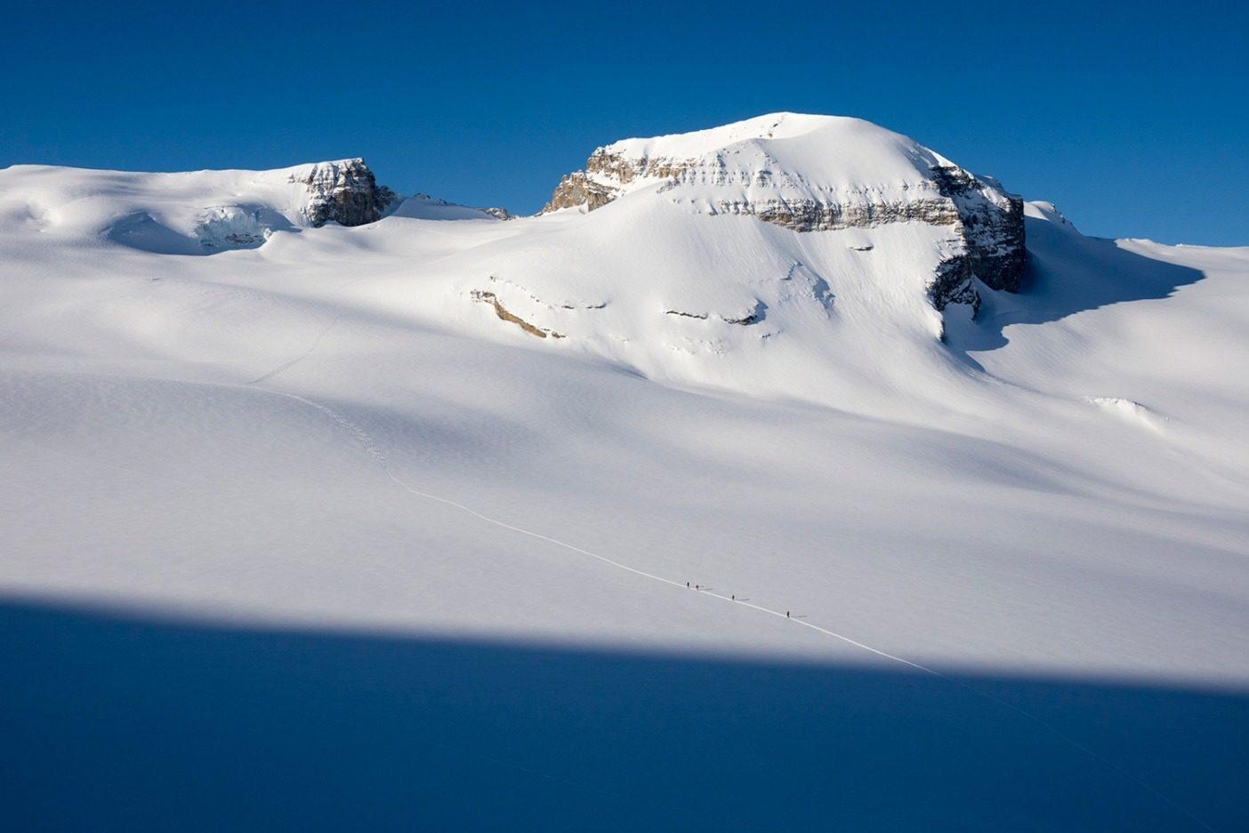 ロンダ山に向かって行くスキーヤーの一行。カナダ人のガイドが「今までに経験した中で最高のワプタでのスキーウィーク」と呼んだ、非常に安定した状況で、急傾斜を行き来しながらスキーを楽しんだ1週間の1シーン。この翌晩、一行はボウ・ハットを訪れ、水を求めた後、氷河の高域にあるテントサイトに戻った。氷河での日焼けで目の周りが白く焼け、夜明けから日暮れまで続いた強行日程で疲れ果てていた。Photo:Kennan Harvey