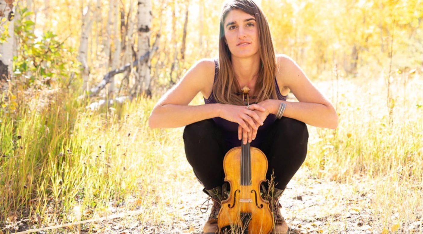アスペンの木々に囲まれて5本弦のLackeyバイオリンを抱くリジー・プロトキン。Photo:Lydia Stern