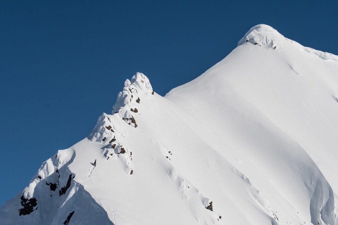 ブリティッシュコロンビア北西部、難しい登りの中で核心に向かってアプローチするライランド・ベル。積雪状態を確かめ、自信を持ってこの挑戦をするのに、数日間のライドと数時間の登山が必要だった。この日、ライランドと兄のタイガ、親友のチャールズ・ピープは、この頂の下にある尾根から数本のライドをした。その後、ライランドは頂上に向かって雪山をブートパックし、空が再び雲で閉ざされる直前にドロップインした。写真:Colin Wiseman