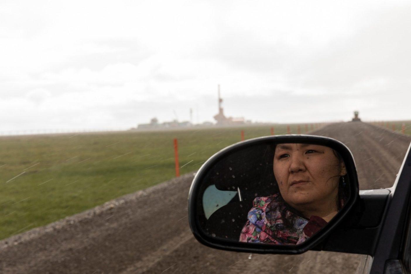 コノコフィリップス社のグレーター・ムースズ・トゥース・ユニットまでの砂利道の脇でカリブーを探すヌイクスト先住民の村の行政官のマーサ・イッタ。イッタは石油とガス開発に反対し、それが村の人びとと動物に与える影響について、意見しつづけている。Photo:Keri Oberly