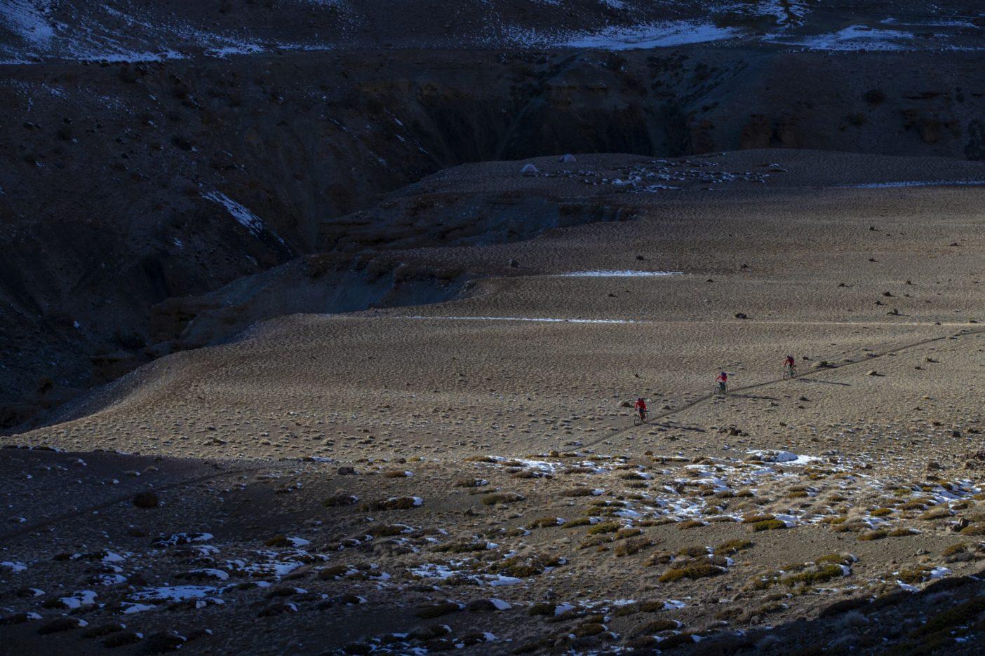 氷点下11度の中で6日目を迎え、その日はまず恐ろしい露出部を数か所通過した。旧サトク村の廃墟を過ぎ、次の難所である8キロ先の2つの鞍部からなる標高5,200メートルの峠を眺められる高台に向けペダルを踏んだ。 前日に標高4,300メートルの峠に2つ登っており、次の食糧投下まで許容できる行程の遅れはもうギリギリだった。危険を冒すよりも、計画を中止し、轍をたどって道路に戻ろうと決断した。賢明で安全な選択と分かってはいても、ザンスカールの古道巡りを夢見て計画に費やしたこの数か月間を棄てることは、悲喜こもごもであった。ライダー:カーストン・オリバー、ニコール・ベイカー、エリック・ポーター 写真 : メアリー・マッキンタイア