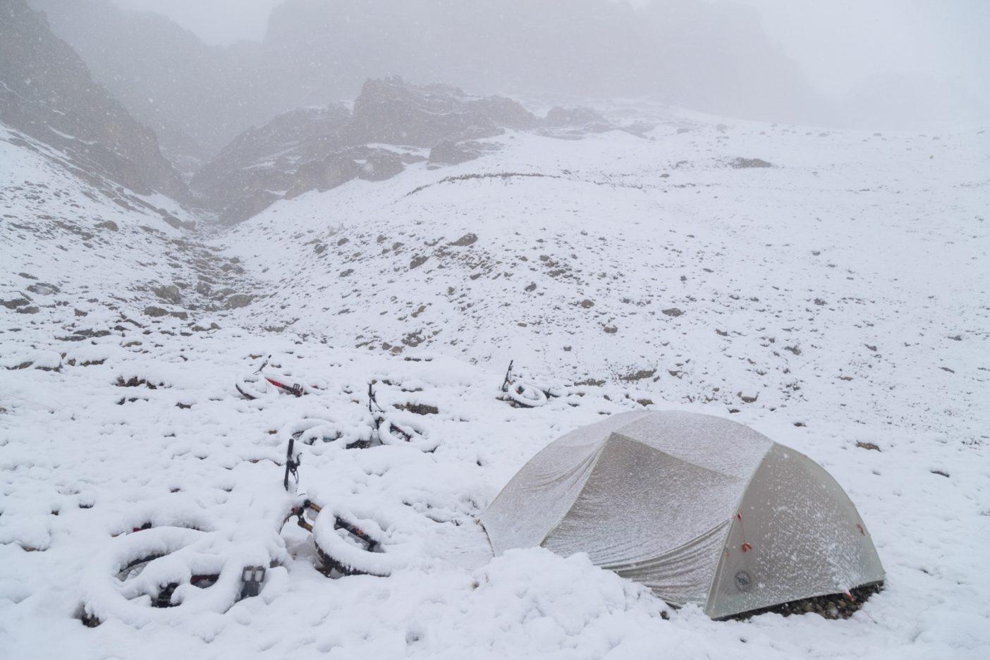 当初の計画では、降車地に正午過ぎに到着し、その日のうちに少し走って数マイルを稼ぎ、よい野営地を見つける時間的な余裕があるはずだった。しかし、吹雪のため数時間余計にドライブすることになり、到着した頃はもう暗くなりかけていた。数インチ積もった雪で山道はほとんど見えず、結局、道路から90メートルほど離れた15度の斜面にテントを張った。その後12時間にわたり60センチ以上の雪が降り、私たちは数時間おきに起き(寝ている間に押しつぶされないように)テントに積もった雪を蹴散らさねばならなかった。この最初の夜の状況は次の日も続き、私たちはうずくまり天候回復を待った。外で吹き荒れる高山の嵐を避けられるなら、頼りない防具もありがたかった。写真 : メアリー・マッキンタイア