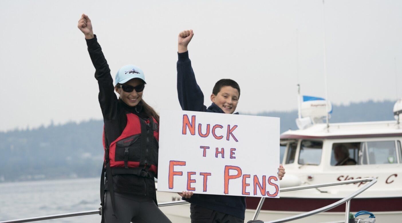 ワシントン州のベインブリッジ島のすぐ脇にあるピュージェット湾の、クック・アグリカルチャー社の囲い網アトランティックサーモン養殖場に、活発に反対する著者の子供スカイラとウエストン・トミネ。Photo:Ben Moon