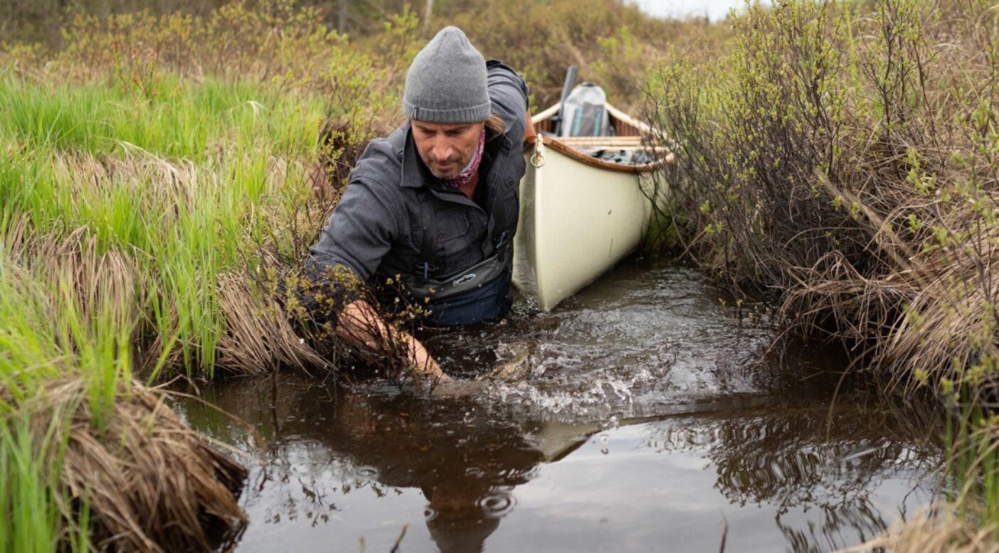 ブーツは水に、オールはバウシートに。狭く湿った連水陸路を航行するナサニエル・リバーホース・ナカダテ。Photo : TONY CZECH
