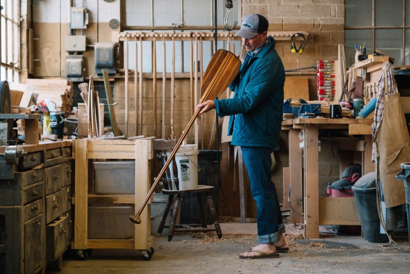 新たに完成した152センチのカヌーの筋肉稼働エンジンの線の美しさに間違いなく惚れ込む著者。ミネソタ州ウィノナのサンボーン・カヌー・カンパニー Photo : TONY CZECH