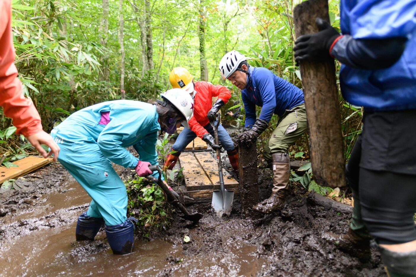 事前に決めておいた場所に木材を設置していく。ぬかるんだ地面は泥の川のよう。 写真:下山 展弘
