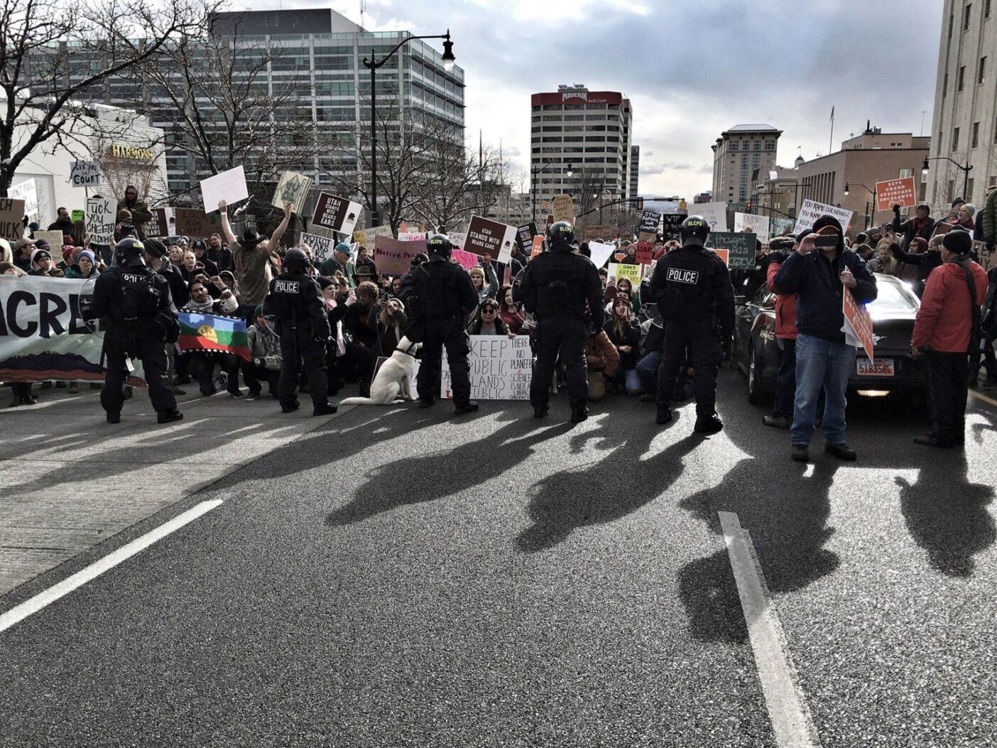 2017年12月4日にソルトレイク・シティで街頭の抗議者と対決する警察。これは『パブリック・トラスト』の撮影の初日で、トランプ大統領が、法的正統性が疑問視されるベアーズ・イヤーズとグランド・ステアケース・エスカランテ国定公園の削減を発表するためにソルトレイク・シティに到着した日だった。