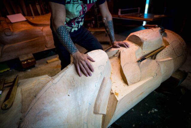 アラスカ州のハイダバーグの共有の納屋で彫ったワスゴ(またはシーウルフ)のトーテムポールを横たえるスグワアヤアンズ・ヤング。この地域に住むハイダ、トリンギットとチムシアン先住民族にとって、トーテムポールは奉献し、歴史を記録し、統治を設定し、重要な物語に実態を与え、羽飾りを陳列する習わしだ。Photo:Bethany Goodrich