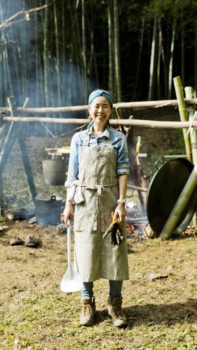 焚き火料理に欠かせないのは、ガンガン使っても直火で焦げてもへたらない、丈夫で使い勝手のいいワーク・エプロンだ。愛用の一枚を身に着けて。写真 : 五十嵐 一晴