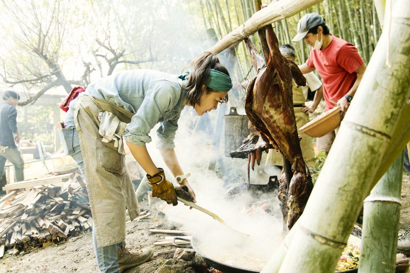 焚き火でシカ肉のグリルとパエリアを仕上げる。竹のアーチは、三上さんと仲間たちが「Ome Farm」敷地内の竹林から竹を切り出し、加工したもの。薪は三上さんが近隣をまわってかき集めた端材だ。写真 : 五十嵐 一晴