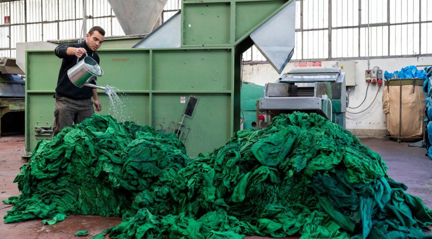 細断機にかける準備としてリサイクル・ウールの端切れに水を噴射し、静電気を防止するガブリエル・ミケローニ。衣類のリサイクルは、それを回収し、分別し、細断し、梳き、紡ぎ、織り、布地を新たな生命へと準備する専門ビジネスのネットワークに依存している。イタリアのプラートにあるこの機械はリサイクル・ウールの細断に使用される。Photo:Keri Oberly