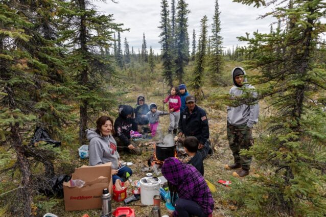 ベリー摘みから一息つき、火のうえで料理したムースのスープを食べるギルバート一家と友人たち。伝統的な食物を料理するときに好まれる方法だ。グウィッチンは子供と孫の未来を心配する。もし北極圏国立野生生物保護区が石油とガス開発に解放されたら、彼らの民族の存在とアイデンティティーそのものを脅かすと信じるからだ。グウィッチンにとって野生は贅沢なものではなく、生活様式そのものなのだ。Photo:Keri Oberly