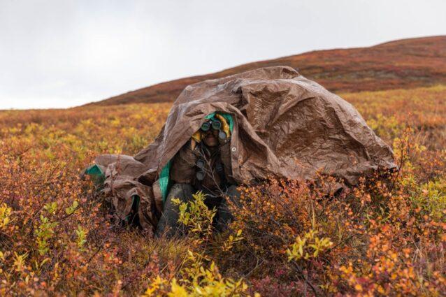 天候の回復を待ちながらカリブーを探して近くの尾根を見張る、伝統的なハンターのグレゴリー・ギルバート。グウィッチン族はアラスカ北東部とカナダの北西部にまたがる15の村に住み、それぞれがポーキュパイン・カリブーの群れの移動ルートに沿ってつくられた。今日、地球温暖化の影響により、群れが通過するのは数村のみ。Photo:Keri Oberly