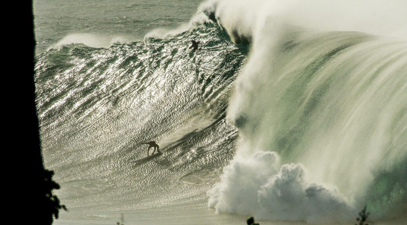 プレートランチを食べにラモン・ナバロを波に乗せるワイメア。ラモンは必死に食らいつく。(2009年のエディにて。オアフ島ノースショア)。写真:スコット・ソーエンス