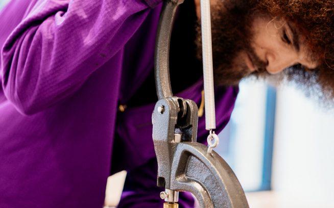 スナップの修理もお手のもの。Worn Wear ツアー中に訪れたカリフォルニア州サンタモニカで、ダウン・スナップT・プルオーバーにやさしく圧力をかけるストア従業員の「TK」ことセロン・ブラウン。フィールドでギアを遊ばせつづけることは、廃棄物の発生と水の使用量、そして総体的なカーボンフットプリントの削減につながる。Photo: Donnie Hedden