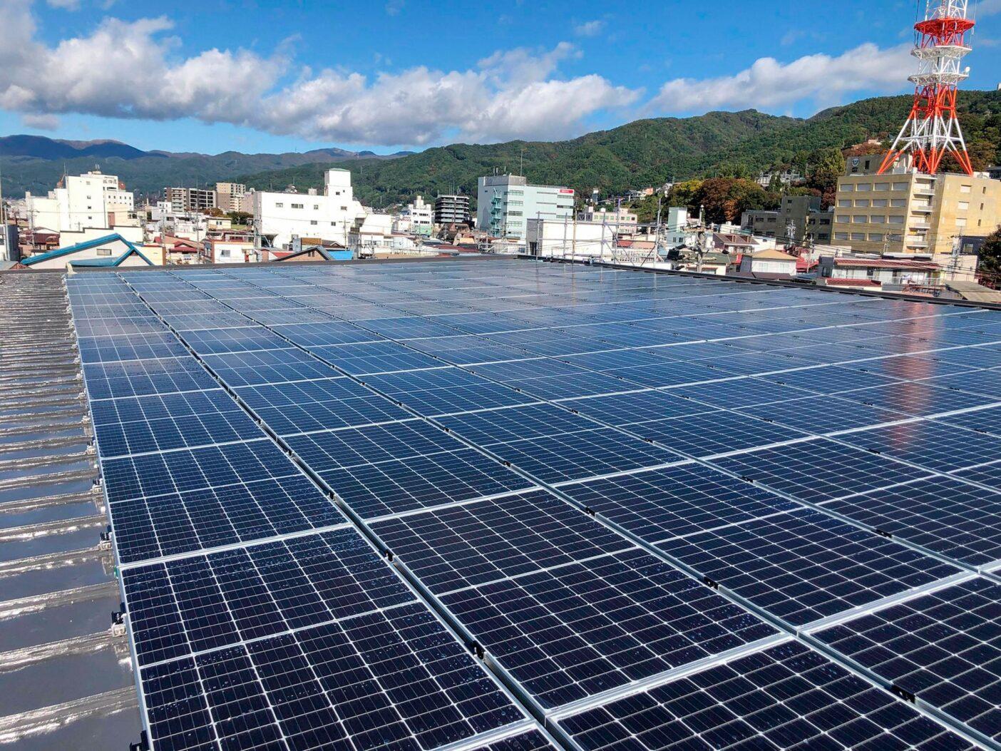 日本で最も日照条件の良い都市の1つである長野県上田市では、屋根、太陽エネルギー、売電収入を組み合わせるという1人の女性のアイデアから、市民主導の発電事業「相乗りくん」が生まれ、2021年1月現在、共有システムに合計約830キロワット分の電力を普及させました。写真は長野県諏訪市街の様子。写真:リビルディングセンタージャパン提供