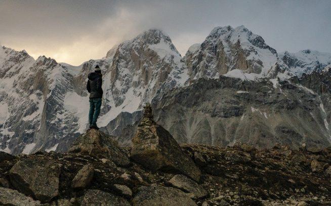 パキスタンのカラコルム山脈でプマリ・チッシュの南峰と東峰の頂を見上げるアン・ギルバート・チェイス。2007年、フランス人アルピニストのクリスチャン・トロムスドルフとヤニック・グラツィアーニが、南峰をアルパインスタイルで6日間かけて登頂。アン・ギルバートとジェイソン・トンプソンとシャンテル・アストーガの最初の目的は南峰だったが、到着後、未登のプマリ・チッシュ東峰に挑戦することを決めた。Caption & Photo : Jason Thompson
