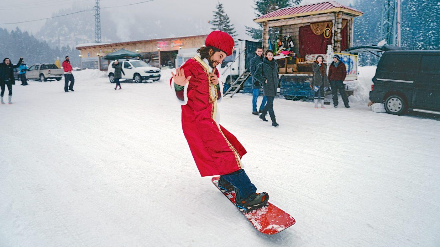 コスチューム写真のブースから借りてきた地元トルコの衣類をまとい通りを滑るアレックス。すべてはスノーマン・フェスティバル(のちに雪だるまとは無関係だということが明らかになった)の一部だ。彼がトルコ、ペトランへの旅で制作に取り組んだ『Foothills: The Unlinked Heritage of Snowboarding(フットヒル:スノーボードの分断化された歴史)』は、地元民が300年以上もスノーボードをしてきたことについての映画だ。Photo:Wade Dunstan