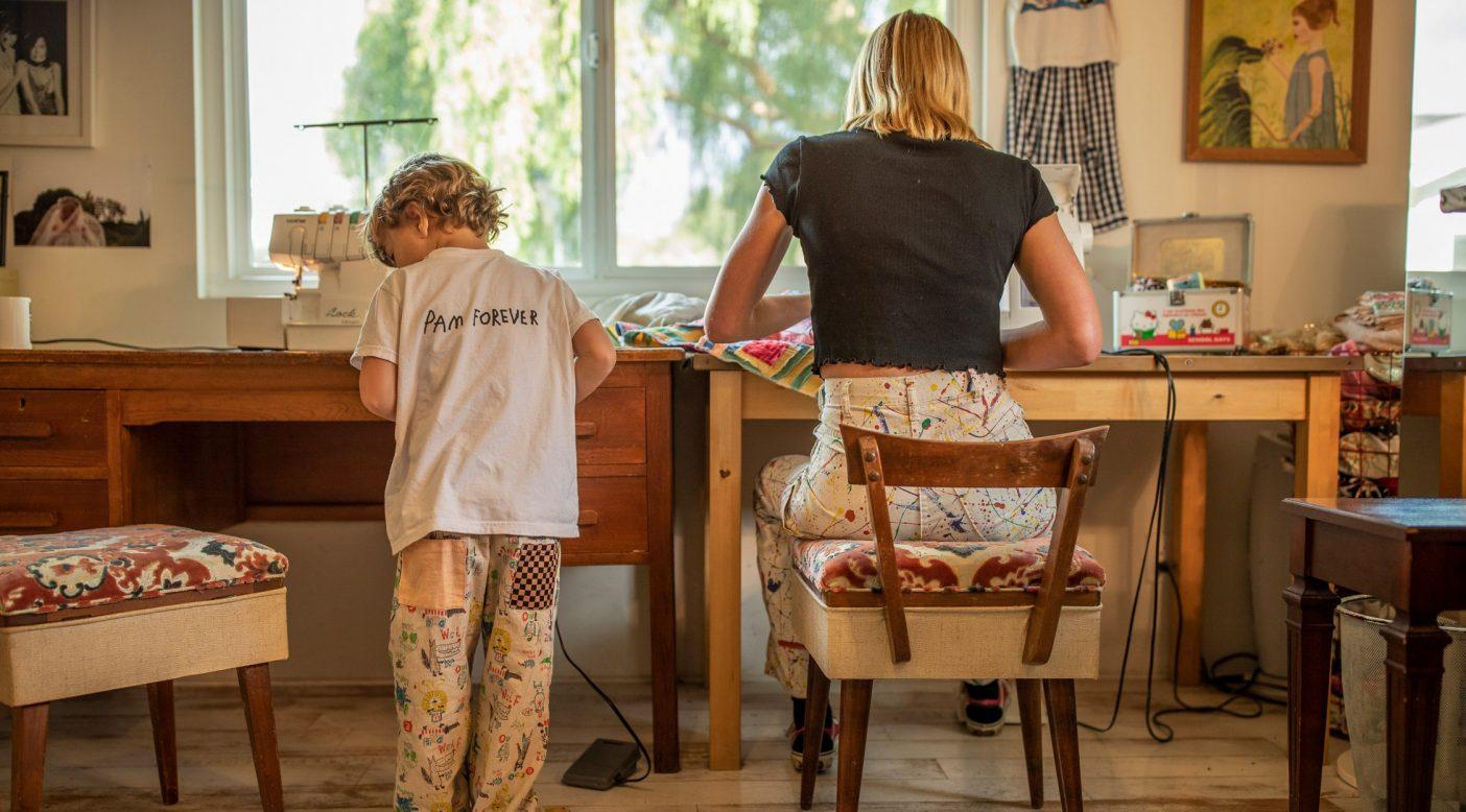 血は争えない。コートニー・レイノルズが地元のフリーマーケットで手に入れたキルトで双子の娘のジャケットを縫う間、息子のサミーは子供用のミシンで自分の作品を縫い始める。Photo: Tim Davis