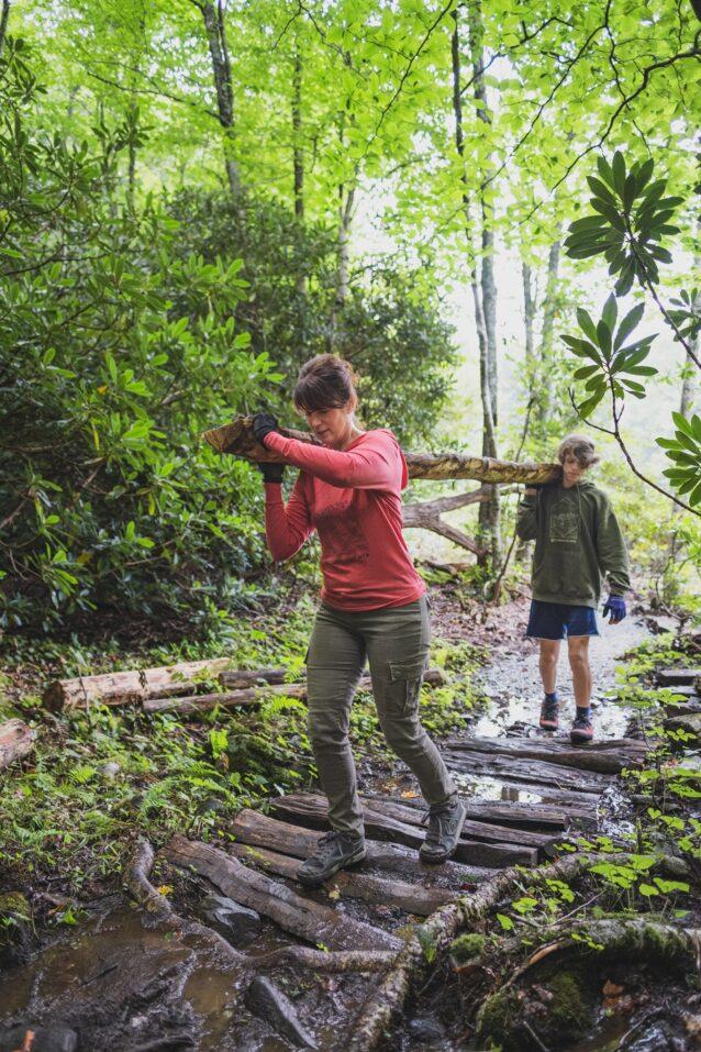 アパラチア南部では、永久に残るものを造りたいなら石を使え、10年余分に長持ちするものを造りたいならニセアカシアを使え、と言われている。ノースカロライナ州ブーン郊外にあるトレイル網のロッキー・ノブ・バイク公園の木道に使うため、地元のニセアカシアの木を肩に担いで運ぶアレシア&サイラス・ジャクソン。Photo:TJ Kearns