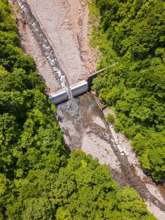 スリット化した砂防ダムを俯瞰で見る。湛水部を埋め尽くした土砂は、時間をかけてスリットを通過し、下流部の河床低下を徐々に戻していく。ちなみにダム右側に設けられた魚道は機能していない。維持さえも困難な構造物だ。写真:奥本 昌夫