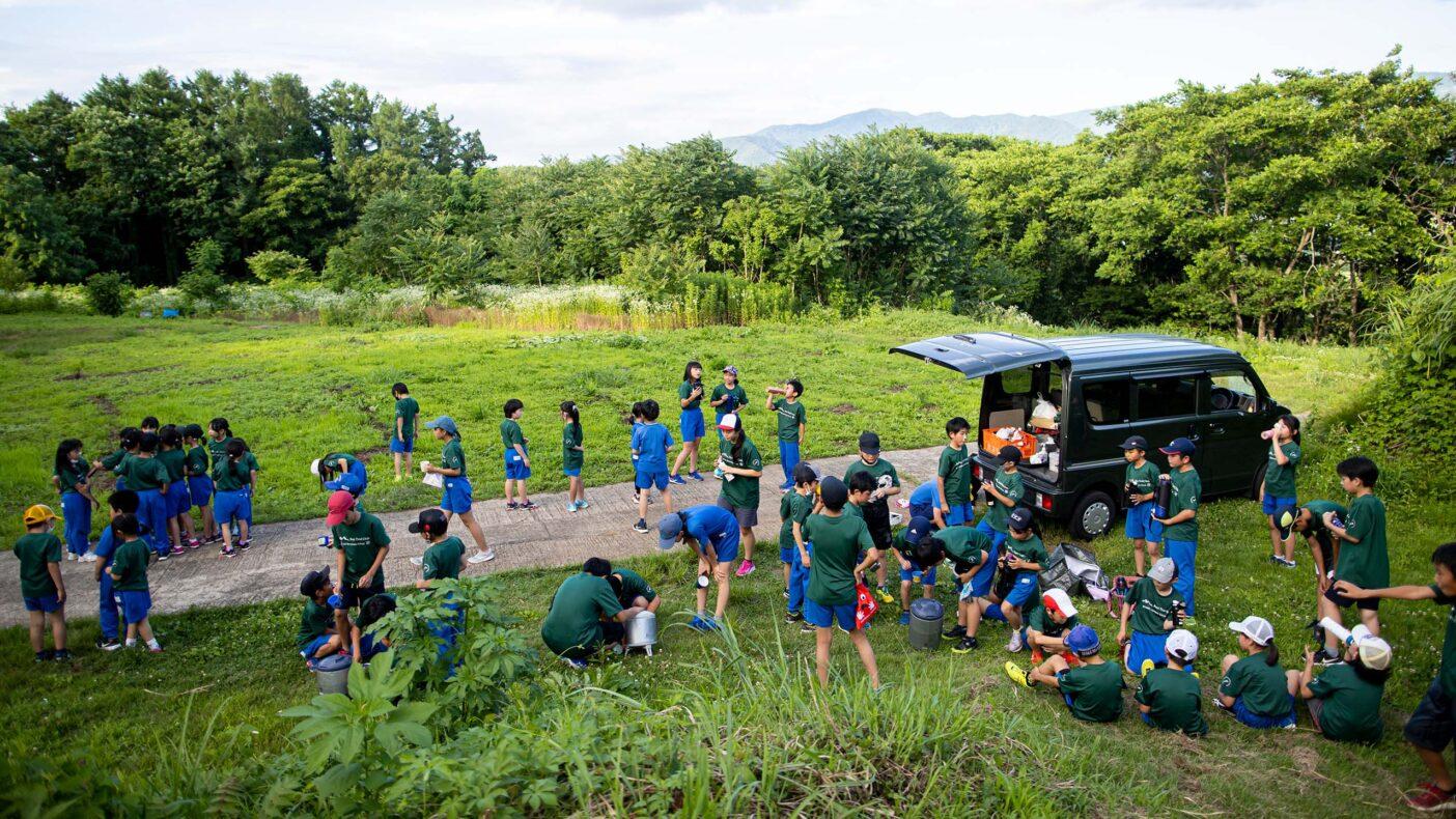 小学校近くにある里山でトレーニング。休憩タイムのドリンクは運営の大人たちが用意する。写真:藤巻 翔