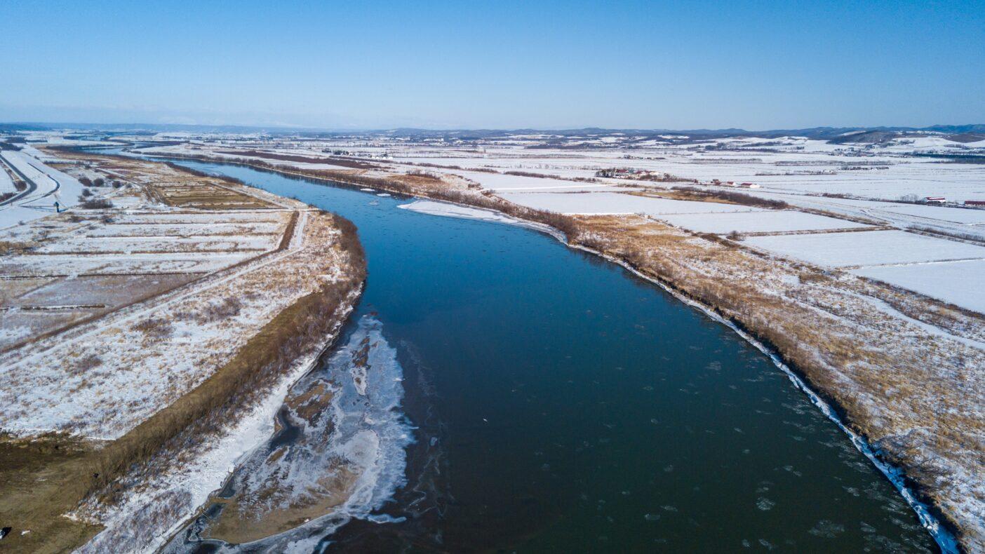 北海道東部を流れる大河川・十勝川。かつては蛇行していたが、広大で肥沃な十勝平野は隅々まで農地化開発が行われ、河川は直線化された。大きな堰堤の下流部に、かろうじてアメマスの生息する余地が残された。写真:奥本 昌夫